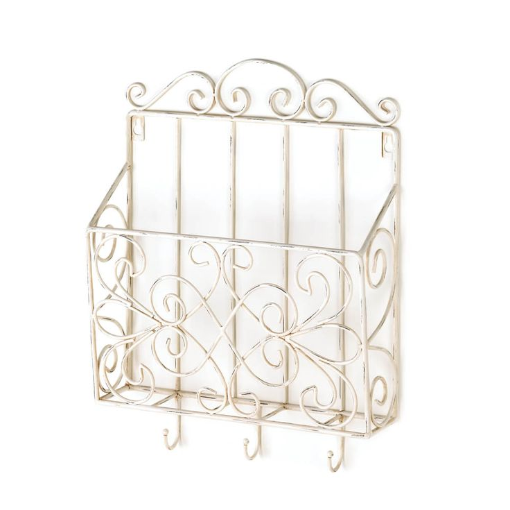 COTTAGE CHARM WALL RACK Keep magazines, today's mail or your daily must-haves organized with this pretty vintage-style wall rack. The scrolling metal frame is painted in weathered white, and the rack features three small hooks at the bottom perfect for hanging your keys, umbrellas, and more.