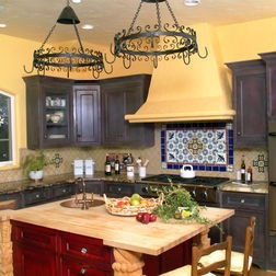 see those pot racks hanging from the ceiling - you could do one of these oer your island.  I kinda like the tile over the stove - not those colors, but it's a neat idea.  And tile is super easy to clean!