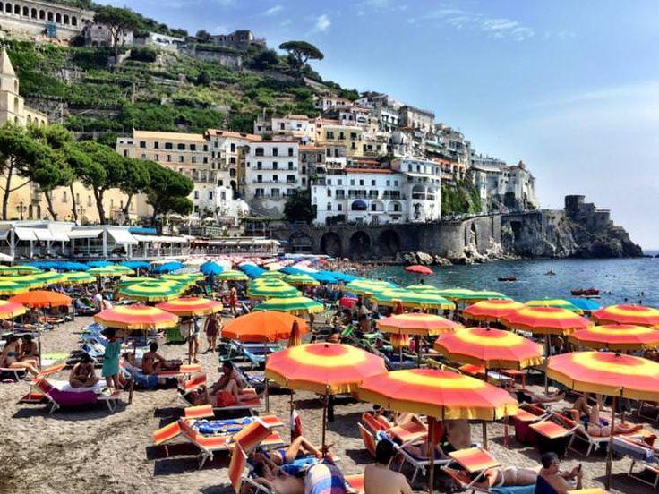 Beachgoers relaxing under umbrellas on the Amalfi Coast. Image by Mark Waind / EyeEm / Getty