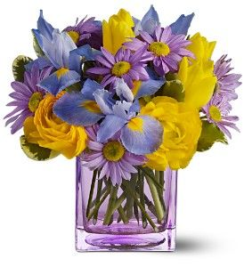 A great centerpiece for a spring event, iris, tulips, ranunculus and daisies are arranged in a colorful glass cube.