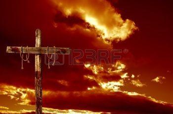 croix en bois: Une croix vide sanglante contre un représentant ciel nuageux rouge au lendemain de la crucifixion de Jésus-Christ Banque d