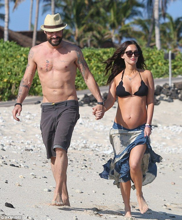 Something to tell us? Megan Fox and husband Brian Austin Green quashed rumors they are still planning to divorce as they walked hand in hand on a beach in Hawaii on Saturday