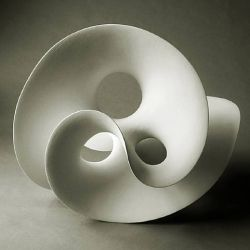 Graceful, curving organic shapes. White, matte ceramic sculpture with great lines. By Eva Hild