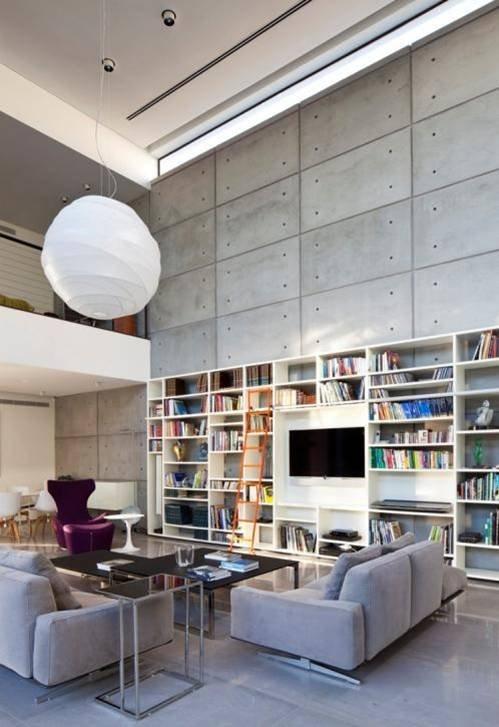 Haifa House   Pitsou Kedem Architect. Living room double height. Library bookshelf. Built in. Concrete. White shelving.