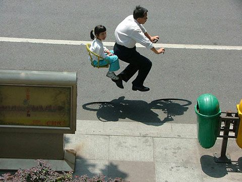 Chinese photographer Zhao Huasen has manipulated photographs to make it look like commuters in China are riding around on invisible bikes.