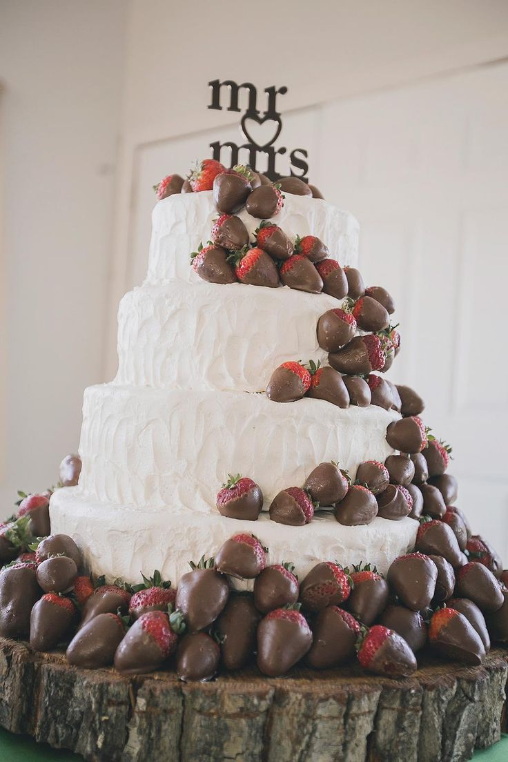 white wedding cake with chocolate covered strawberries
