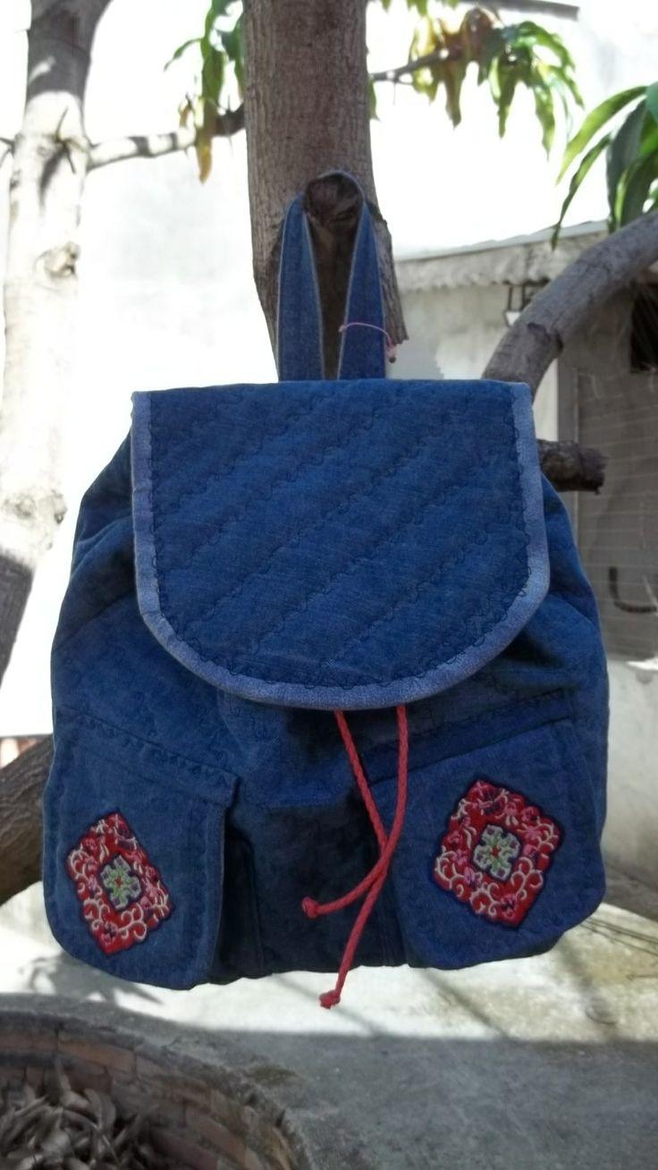 Mochila feita em jeans denim, com dois bolsos frontais com detalhe bordado, amarrada com uma trança em couro ecológico, forrada com tecido impermeável. Dentro há um bolso fechado por zíper. Alças reguláveis.