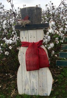 Bonhomme de neige fabriqué à partir de bois de palettes récupérées. Il a un…