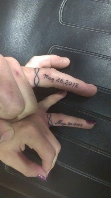 Mine and my husband's Infinity band and wedding date ring finger tattoos