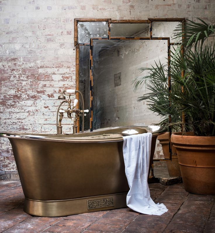 2017 Bathroom trends: Warm brass is ideal for styling with large-scale ferns for a tropical theme - the Catchpole & Rye Brass Bateau, shown with a brushed brass finish is styled with exposed brickwork.