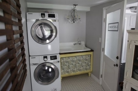 great farmhouse sink in a laundry room.  Fold up drying rack on wall.