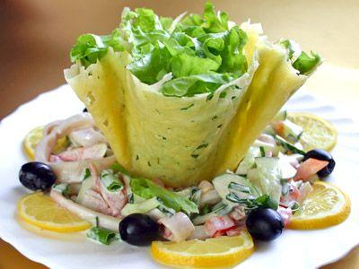 Салат из кальмаров в сырной корзинке 100 г сыра «Пармезан»,1 пучок листьев зеленого салата,1 банка конс.кальмаров,1 огурец,1 помидор,1 пучок зеленого лука,1 ст.л. майонеза,соль,черный перец,ломтики лимона,маслины для украшения. Корзинка:сыр насыпать на сковороду и когда он подтает перевернуть блин на стакан. Ингридиенты смешать и выложить в корзинку