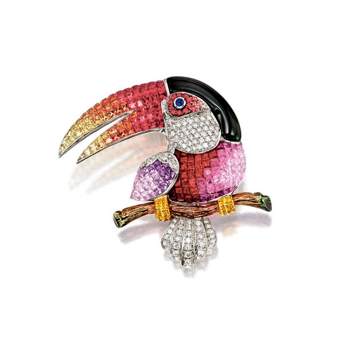 Modelled as a toucan perching on a branch, the body, beak and wings set with calibré-cut coloured sapphires, decorated to the eye and surround with cabochon sapphire and circular-cut coloured sapphires respectively, the cheek, shoulder and tail encrusted with brilliant-cut diamonds, the crest fitted with a carved onyx, the sapphires and diamonds together weighing approximately 10.00 and 1.00 carats respectively, mounted in 18 karat white and yellow gold