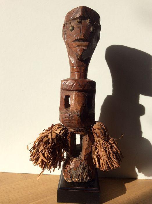 """"""" Nkisi """" Krachtbeeld - TETELA/SONGYE - Ex. Belgisch Congo.  De beelde der TETELA vertonen zeer uiteenlopende stylkenmerken  afhankelijk van de naburige groepen.In ons geval gaat het duidelijk om de KUSU/SONGYE invloed.De staande fetisch  met de handen op de buik  heeft een grote opening bovenaan het hoofd en kleine openingen in de navel en oren voor het """" bishima """" - krachtmateriaal.De ogen zijn messingspijkers en op het voorhoofd werden zes gaatjes  gevuld met dierlijke pelsharen…"""