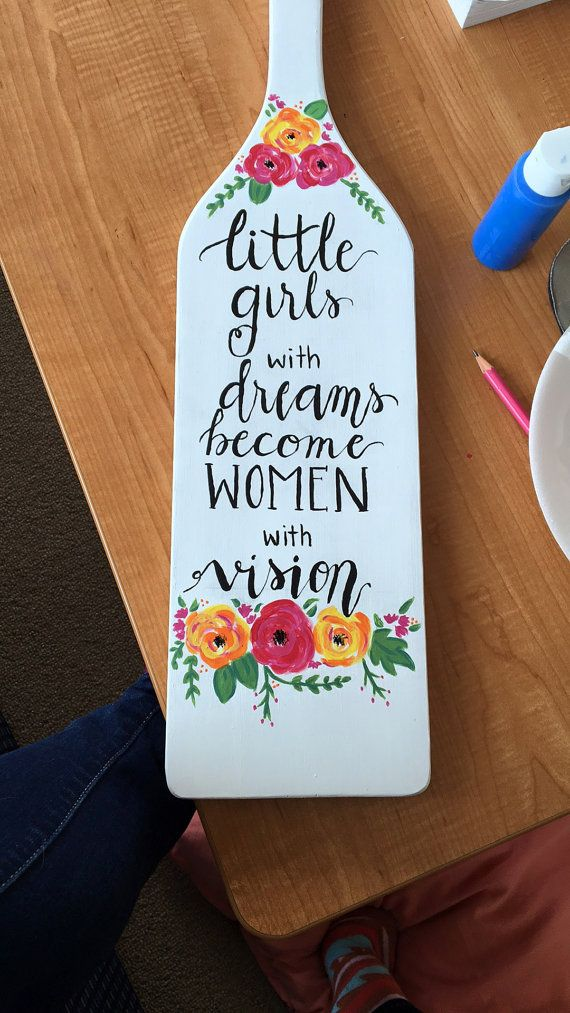 A handwritten calligraphy quote on any colored background with any colored text with flowers on the top and bottom of the quote. Details about the paddle - Design on the front only - Back of the paddle is painted any solid color - Embellishments such as pearls, rhinestones, bows, etc can be added - Different types of lettering can be used to say anything that youd like