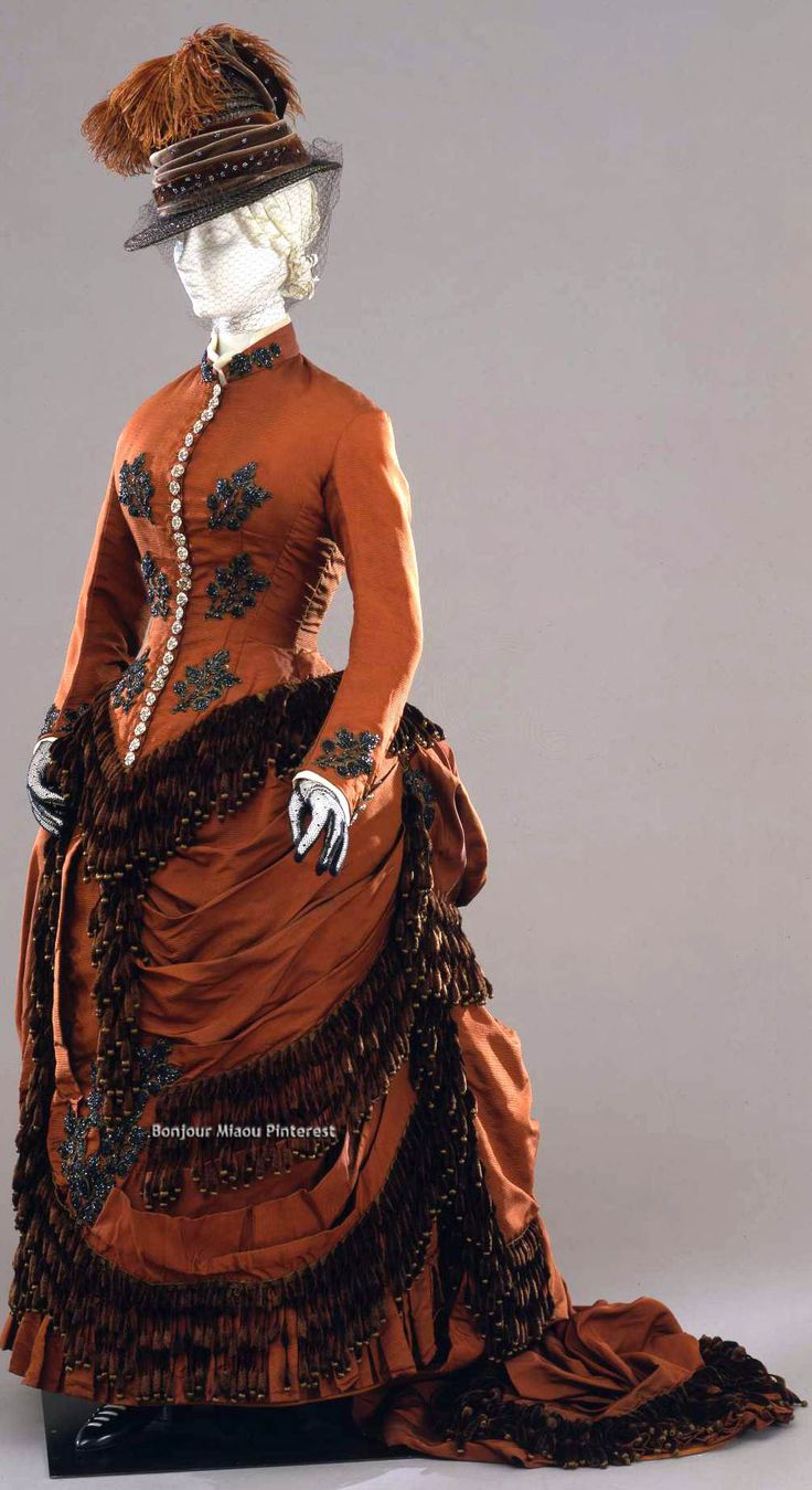 Walking dress, Liguria, Italy, ca. 1880-82. Embroidered brown silk with ecru tulle and chenille fringe. Bodice closes front with 30 buttons. Galleria del Costume di Palazzo Pitti via Europeana Fashion