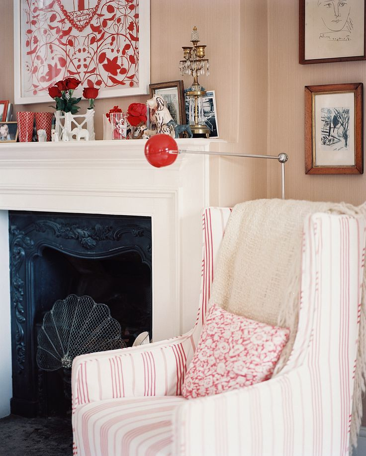 Country Traditional Living Room: A striped armchair beside a red floor lamp and a white mantel.