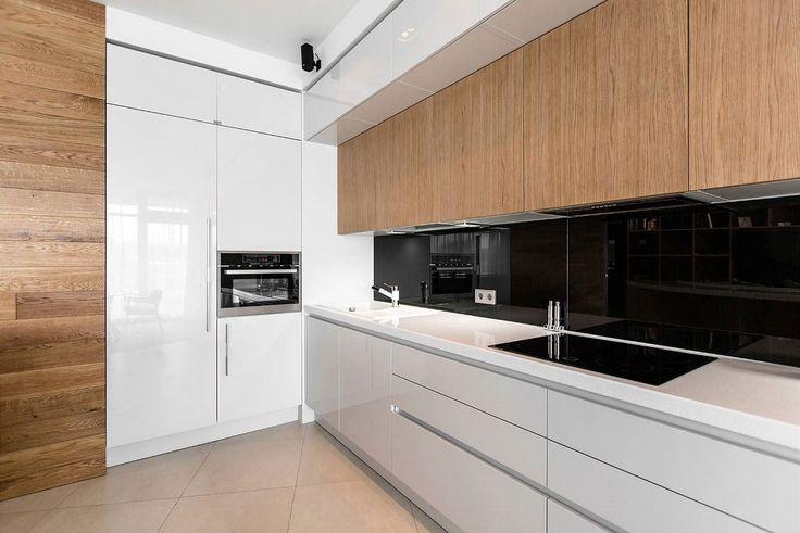 Kuchyňský kout v sobě kombinuje lesklé bílé skříňky a dřevo.
