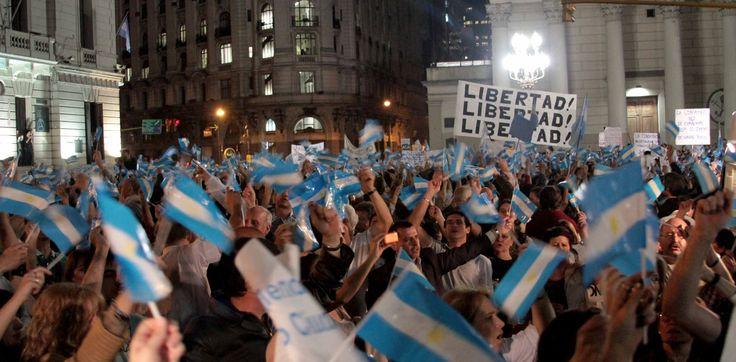 En esta imagen captada en Plaza de Mayo, podemos ver un acontecimiento de carácter social, donde ciudadanos se manifestaban en repudio de las medidas adoptadas por el gobierno durante Diciembre del 2001.  Dicha fotografía se muestra como un icono, donde podemos encontrar símbolos convencionales, como banderas y escrituras, y en el rostro de las personas vemos un índice de indignación y angustia.