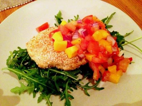 Laxbiff med sesamfrön och het mangosalsa    TilIngredienser    Till biffarna  200 gram lax  1 litet ägg  Ev 2 krm sesamolja  2 msk sojamjöl  Ev en halv chilifrukt  Sesamfrön till panering  Olja till stekning    Till salsan  2 tomater  En halv rödlök  1 avokado  En halv röd chilifrukt  125 gram mango (fryst eller färsk)  2 msk rapsolja  En halv lime  Salt och peppar    Till servering  Ruccolasallad och en halv lime    Gör så här    Börja med salsan. Klyfta tomaterna och skär ut innanmätet…