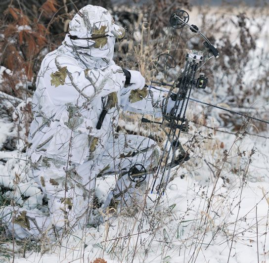 A hunter wearing Realtree AP ™ Snow camo rests on one knee and prepares to draw his bow amidst ...