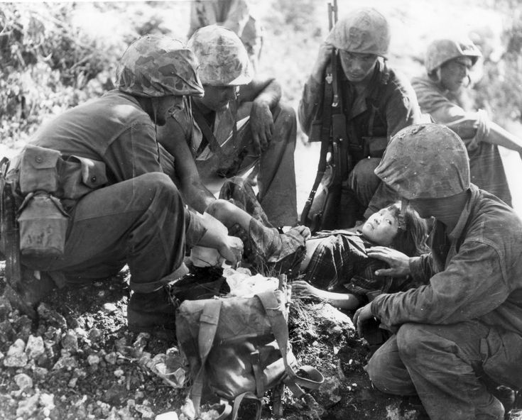 "US Marine and Navy corpsmen assist an injured Japanese child in Saipan, 1944. Note their camouflage helmet covers that helped distinguish them from US Army personnel. The Japanese army routinely refused help to their own civilians and often shot wounded people so they wouldn't fall in the hands of the ""bestial Americans."""