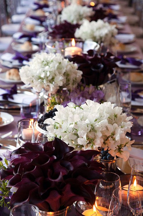 A long wedding table is covered with white sweet peas and passion calla lilies.