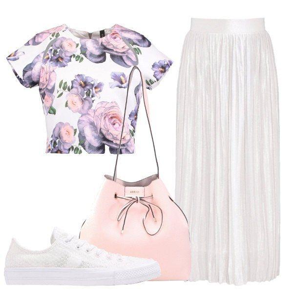 Outfit composto da gonna lunga e ampia bianca, crop top a maniche corte e fantasia floreale, borsa a secchiello rosa e sneakers basse della Converse bianche.