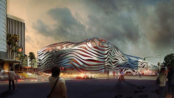 Архитектурная фирма Kohn Pedersen Fox намеревается окружить автомобильный музей Petersen Automotive Museum в Лос-Анджелесе стальными лентами, кардинально изменив облик здания. Интегрированные светильники будут освещать постройку изнутри ярким красным светом,который будет проникать сквозь ленты.создавая яркий,запоминающийся образ.