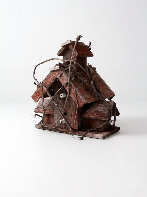 A vintage folk art birdhouse. The large rough hewn wood house features wood vines arching and rolling over the frame and faint red paint. It features