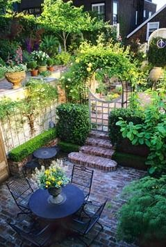 Overview of urban courtyard garden with brick paved terrace with table and chairs. Steps and arched gateway to raised patios - San Francisco, California, USA