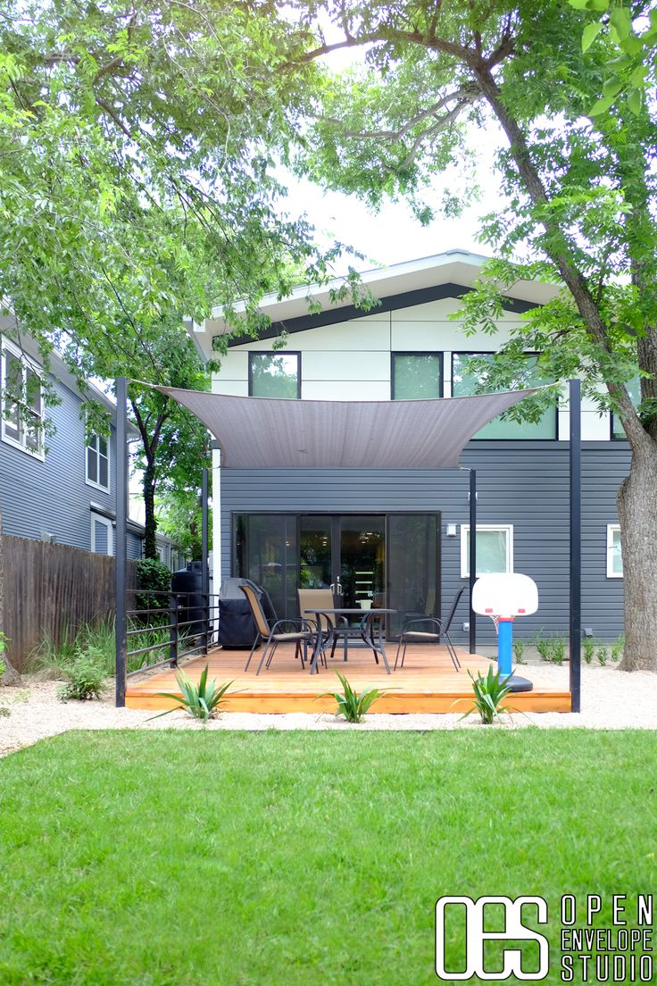OES | Cedar deck with steel rails and shade sail on steel posts, pea gravel, native plants and steel-edged grass