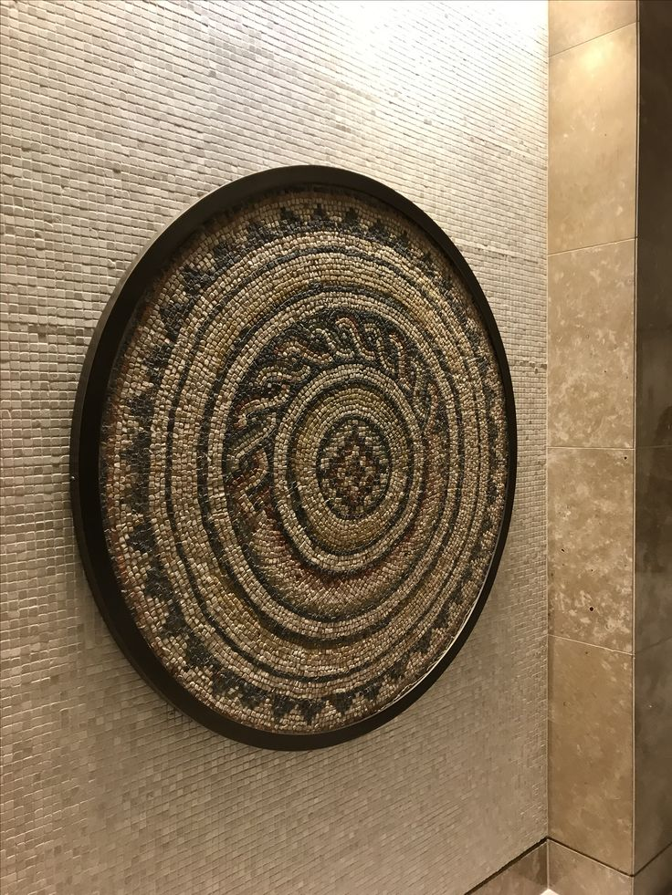 Photo 2: Mosaic wall feature at Crown. This statement piece draws the attention of the viewer with its mandala style pattern and raw stone texture. It is mosaiced from small stones in neutral tones to tie in with the overall feel of calmness and serenity of this spa space.