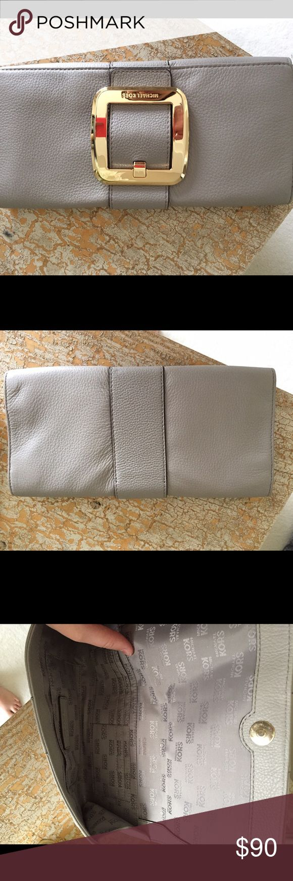 Michael kors clutch Grey clutch with gold buckle. Great condition used only once. Perfect for evening events or weddings! Color is neutral so you can pair with anything. Michael Kors Bags Clutches & Wristlets