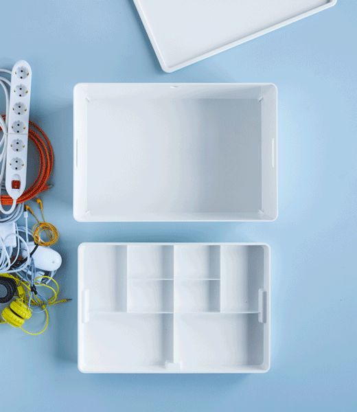 Tech accessories and chargers are stored in a white IKEA KUGGIS box with interior dividers.