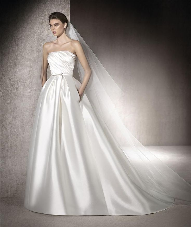 Classic princess wedding dress with pockets in kelly mikado. Draped strapless neckline with discreet belt with a bow that decorates the bride's waist.