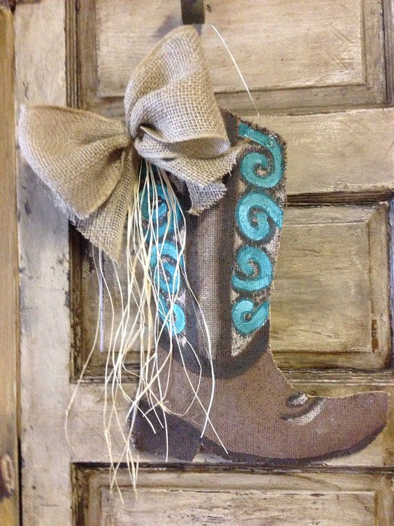 This is a custom cowboy boot door hanger made of burlap, painted with acrylic paint, wire/twine (you pick) hanger for hanging, and accented with a bow