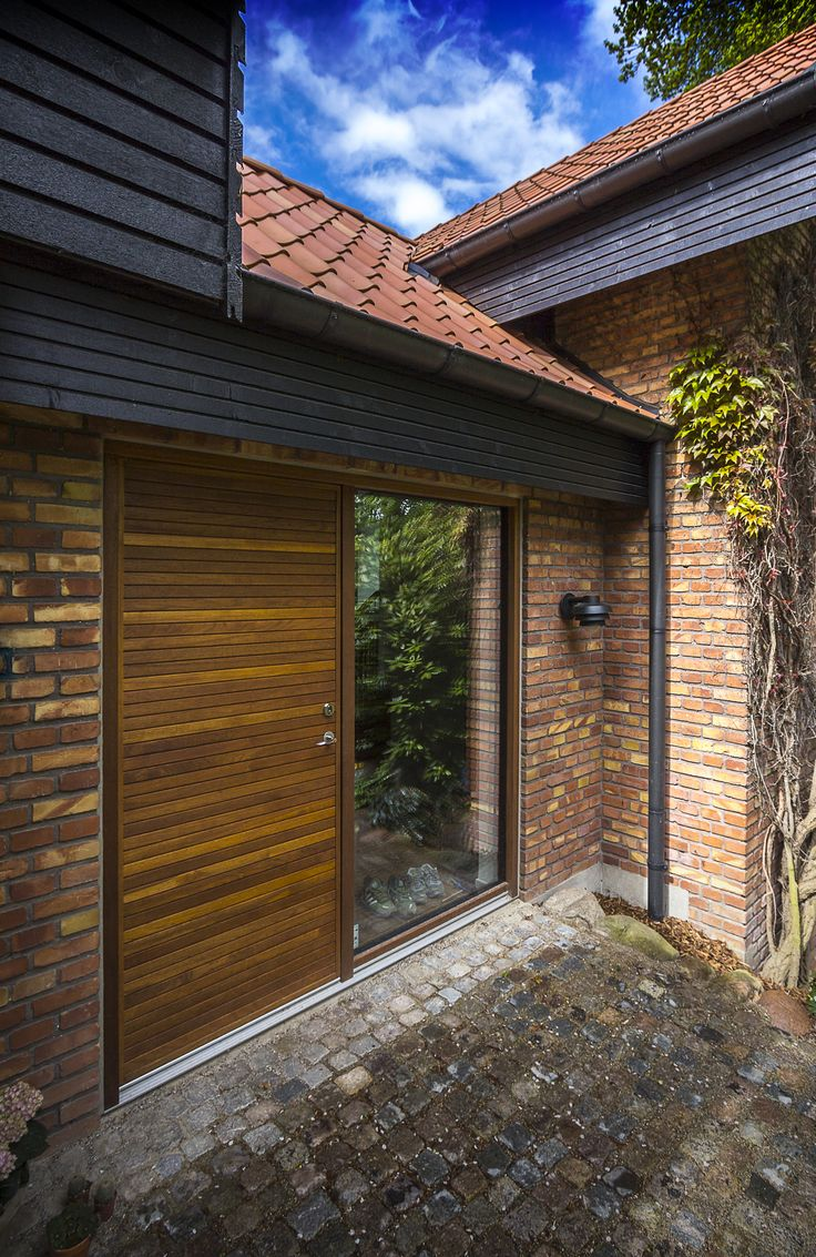 The door fits into the modern architecture, which has a living facade with the spread of colour.