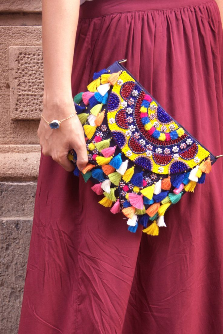 Add an eclectic vibe to any outfit with this pom pom and beaded clutch