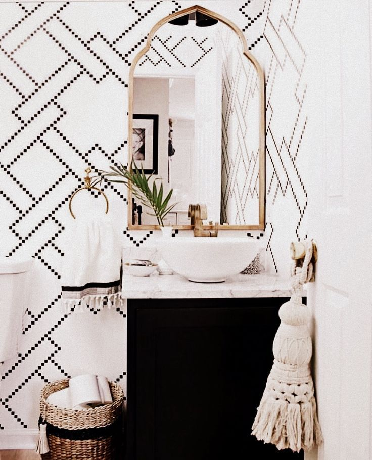 A single stem is a lovely way of decorating a bathroom, particularly in this one with the geometric wallpaper and black/white/gold interior.