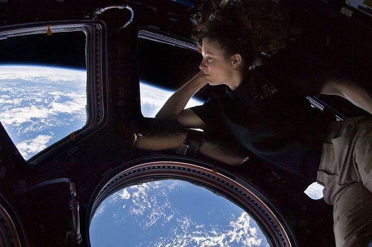 Self portrait of Tracy Caldwell Dyson in the Cupola module of the International Space Station observing the Earth below during Expedition 24.
