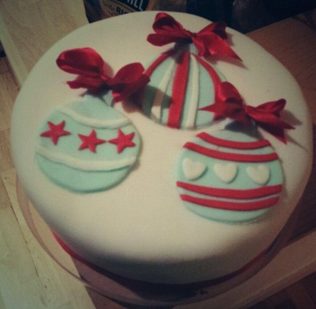 Whisky Christmas Cake with baubles and red ribbons