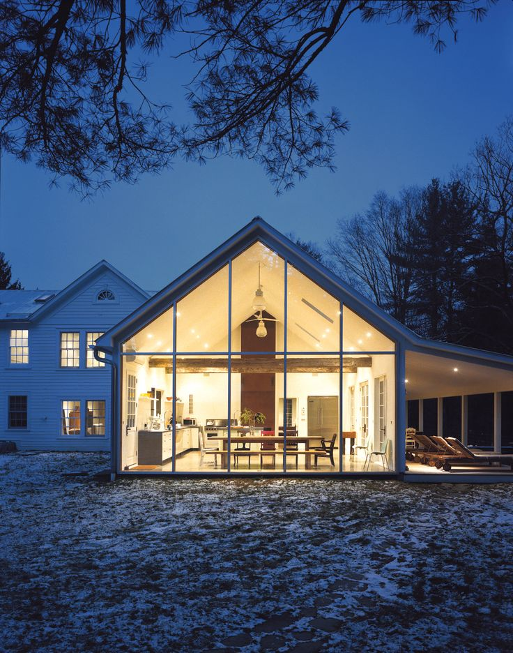 The Floating Farmhouse's semitransparent addition has a roofline that matches the pitch of the original 1820s farmhouse. A porch, tucked under the side eaves, is cantilevered over a stream that runs through the property. Ikea loungers are illuminated from the interior by commercial gymnasium lights repurposed as pendant lamps.