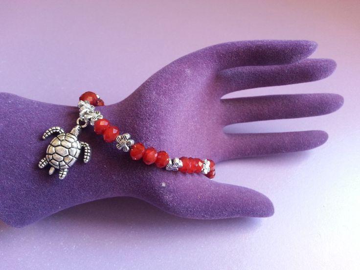 Pulsera de piedras rojas con pequeños pequeñas flores entre medias y una preciosa tortuga de plata. Perfecta para cualquier ocasión.