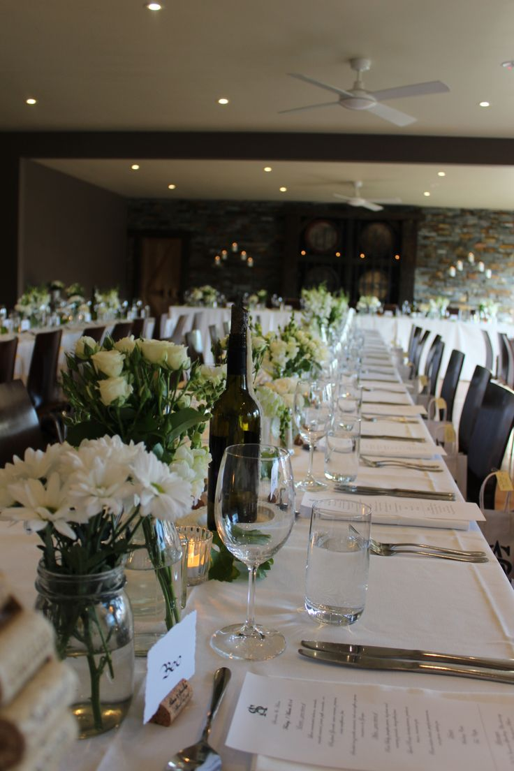 Long wedding tables with white florals. next to our rustic barrel wall backdrop