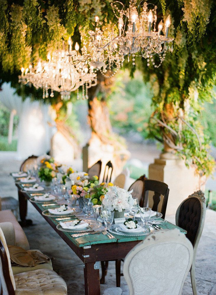 Gorgeous outdoor entertainment setting: love the elegance of the chandelier juxtaposed against the lushness of the vines and shabby chic table and chairs.