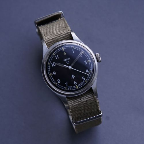 This is a Smiths W10 watch supplied to and issued by the British Army in 1970. Powering the W10 is the cal. 60466E, a 17-jewel manual movement produced in-house by Smiths. 17-jewel, shockproof movement with hacking seconds operated via the button. Black dial with Broad Arrow mark and T within a circle, denoting the use of Tritium (luminous) on the dial and hands. 35mm diameter. We have fully serviced and … Read More →