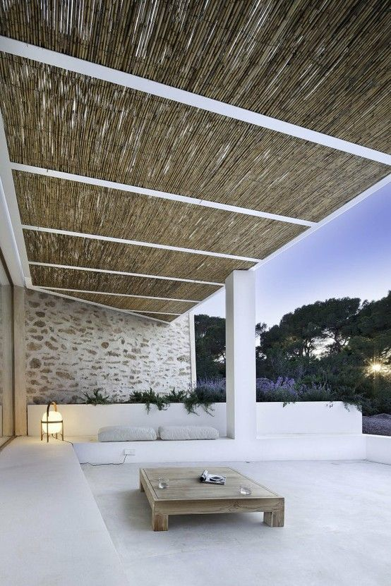 Outdoor white stone wall built in seats and bamboo. expensivelife™