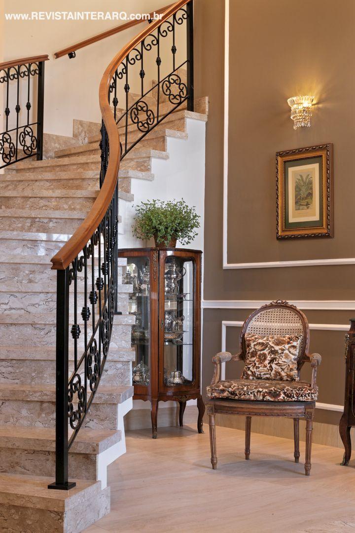 A sinuosa escada com degraus em mármore e guarda-corpo de ferro (Quality Inox) é a estrela do hall de entrada. A pintura escura com detalhes claros valoriza as boiseries