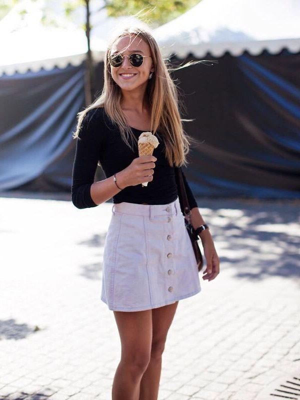 Street style de look trendy e cool, com saia de botões e blusa preta de manga comprida.